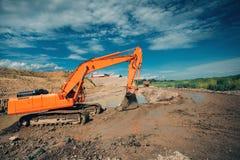 Escavatore che lavora al cantiere della strada principale Dettagli dell'escavatore che scavano in acqua e sporcizia per la costru Immagini Stock