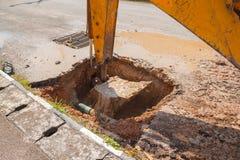 Escavatore che lavora alla riparazione dell'acqua e fognature del tubo sulla strada Immagini Stock