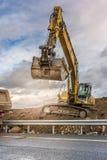 Escavatore che riempie un camion di terra per la costruzione di un pendio per la costruzione di una strada immagine stock libera da diritti
