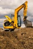 Escavatore che si leva in piedi sul terreno con il motore aperto Fotografie Stock