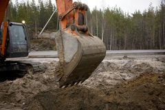 Escavatore con una benna alzata Fotografia Stock