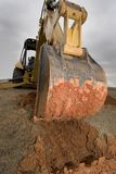 Escavatore a cucchiaia rovescia che scava in sporcizia rossa. Immagini Stock