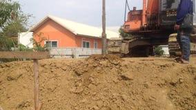 Escavatore a cucchiaia rovescia con un dispositivo di perforazione ad un cantiere stock footage