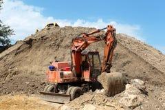 Escavatore da scavare sotto la montagna Fotografia Stock