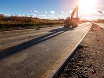 Escavatore del cingolo con il secchio, strada della costruzione Fotografia Stock