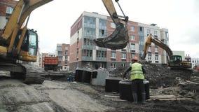 Escavatore di fumo lento del cavo del lavoratore per appendere l'anello concreto della botola sulle catene video d archivio