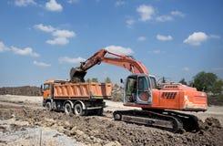 Escavatore e camion che lavorano alla costruzione di strade Fotografie Stock Libere da Diritti