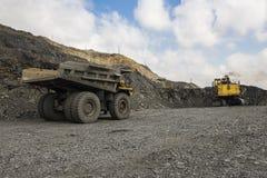 Escavatore e camion nella cava del ferro Immagini Stock Libere da Diritti