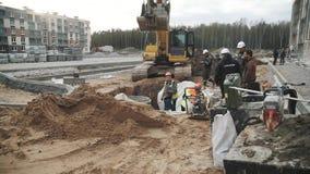 Escavatore e lavoratori lenti in caschi in fossa al cantiere stock footage