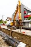 Escavatore giallo al cantiere nell'insediamento urbano fotografia stock libera da diritti