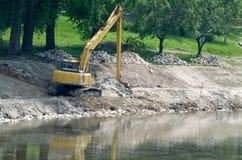 Escavatore giallo alla riva Fotografia Stock