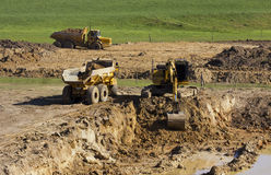 Escavatore giallo e grandi camion gialli Fotografia Stock