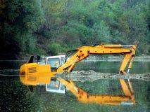 Escavatore nel fiume Immagini Stock