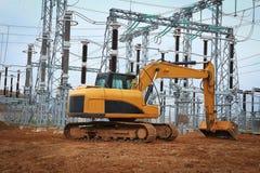 Escavatore nella costruzione industriale della sottostazione elettrica Immagine Stock Libera da Diritti