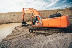 Escavatore resistente ai lavori stradali della costruzione della strada principale Bulldozer ed escavatore che scavano nel suolo Immagini Stock Libere da Diritti