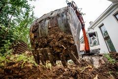 Escavatore resistente industriale che scava al cantiere Primo piano del secchio del metallo e del mestolo fotografia stock libera da diritti