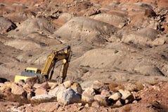 Escavatore su un mucchio della roccia Immagini Stock Libere da Diritti