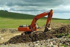 Escavatore sul lavoro nel paesaggio della montagna immagini stock