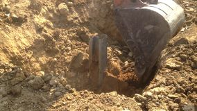 Escavatore sul lavoro pala meccanica che lavora al campo, vangata dell'escavatore a cucchiaia rovescia intorno alla colonna conce stock footage