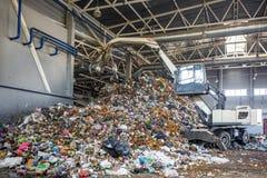 Escavatore sulla separazione primaria dell'immondizia nella pianta di trattamento dei rifiuti Raccolta dei rifiuti separata immagini stock