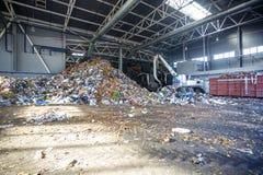 Escavatore sulla separazione primaria dell'immondizia nella pianta di trattamento dei rifiuti Raccolta dei rifiuti separata fotografia stock