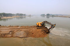 Escavatore in un cantiere della diga Immagini Stock Libere da Diritti