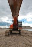 Escavatore in una cava di ghiaia con il cielo nuvoloso Fotografia Stock Libera da Diritti