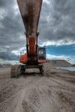 Escavatore in una cava di ghiaia con il cielo nuvoloso Fotografia Stock