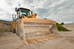Escavatore in una cava di ghiaia con il cielo nuvoloso con una grande pala Fotografie Stock Libere da Diritti