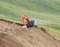 Escavatori che scavano la terra in un campo verde Fotografia Stock
