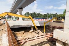 Escavatori che scavano terra nella costruzione del sottopassaggio del tunnel dentro Fotografie Stock