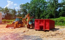 Escavatori del trattore della nuova costruzione dell'escavatore e contenitori gialli dell'immondizia fotografia stock libera da diritti