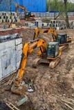 Escavatori gialli che scavano la terra Immagine Stock