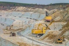 Escavatori pesanti di estrazione mineraria nella cava gessosa Immagini Stock