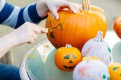 Escavazione fuori della zucca per preparare la lanterna di Halloween Fotografia Stock Libera da Diritti