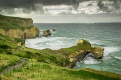 Escave um túnel o tempo nebuloso da opinião da praia, Dunedin, Nova Zelândia imagem de stock royalty free