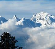 Escena alpina de la montaña del invierno de la nube baja debajo de un cielo azul Fotos de archivo libres de regalías