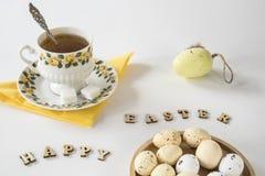 Escena amarilla de Pascua con té, letras y huevos imagenes de archivo
