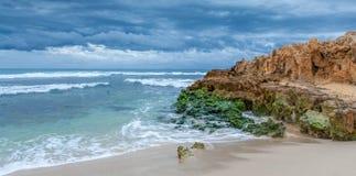 Escena azul de la playa con la roca Imagen de archivo libre de regalías