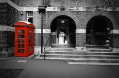 Escena blanco y negro de la calle con color selectivo en una caja roja del teléfono en Sydney, Australia imágenes de archivo libres de regalías
