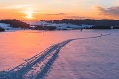 Escena con el rastro en nieve en el fondo de la puesta del sol Foto de archivo libre de regalías