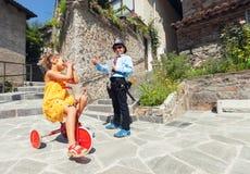 Escena con jugar, el poli y el conductor de los niños en al aire libre Imagenes de archivo