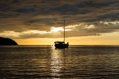 Escena crepuscular del barco con el cielo nublado Foto de archivo