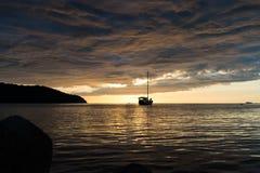 Escena crepuscular del barco con el cielo nublado Fotos de archivo