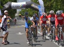Escena de la acción durante la raza, con un ciclista pidiendo agua, durante el evento de Grand Prix del camino, una raza del circ Imagen de archivo