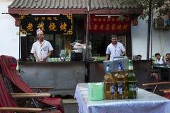 Escena de la calle en la ciudad de Dunhuang, con dos cocinas en una parada de la comida, en China fotografía de archivo