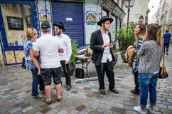 Escena de la calle en Marais con los hombres jovenes judíos ortodoxos que hablan con los turistas Fotografía de archivo libre de regalías