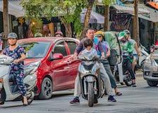 Escena de la calle de Vietnam, montar a caballo de la niña en la vespa de motor con el papá sin casco protector fotos de archivo libres de regalías