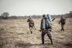 Escena de la caza con el grupo de cazadores con las mochilas y la munición de la caza que pasan a través de campo rural durante t Foto de archivo libre de regalías