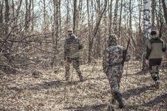 Escena de la caza con el grupo de cazadores en camuflaje que caminan en bosque de la primavera con las hojas secas durante tempor Foto de archivo